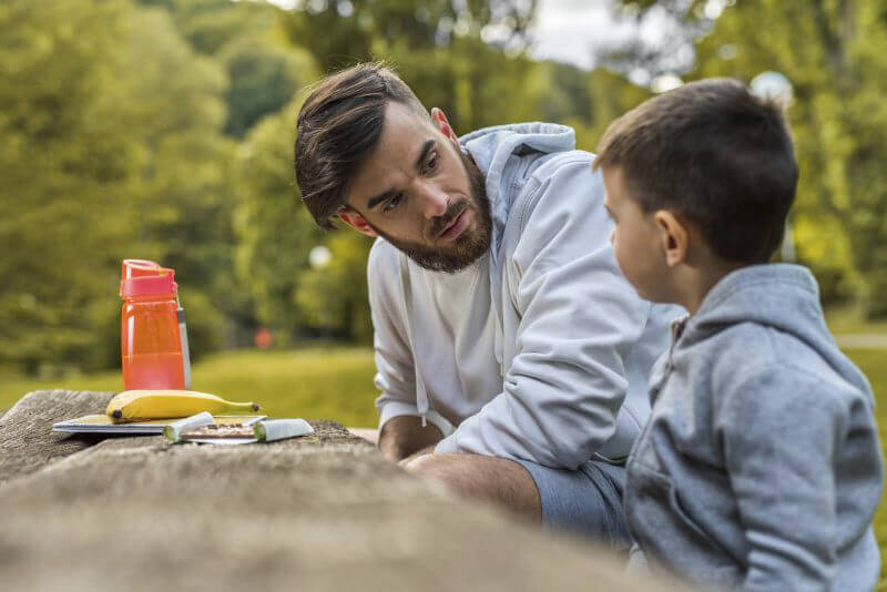 Young man relaxing with his little boy in the park and talking to him.