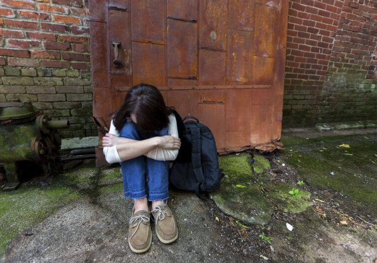 Young teenager down and out in an alley on the street too afraid to allow someone to help her