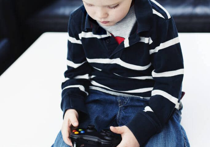 Boy sits all alone in living room and plays a computer game. He is holding a game controller