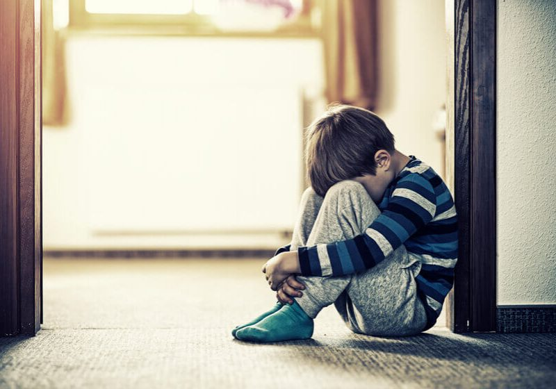 Depressed sad child sitting on the floor, in the door. The little boy is hiding his head between legs.