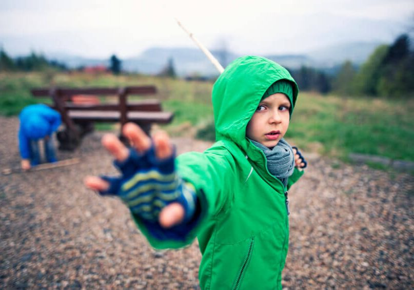Little boys playing jedi knights using sticks and imagination. The boy aged 4 is using his special powers and holding his wooden 'lightsaber'. The boy in the background is picking up his weapon from the ground.