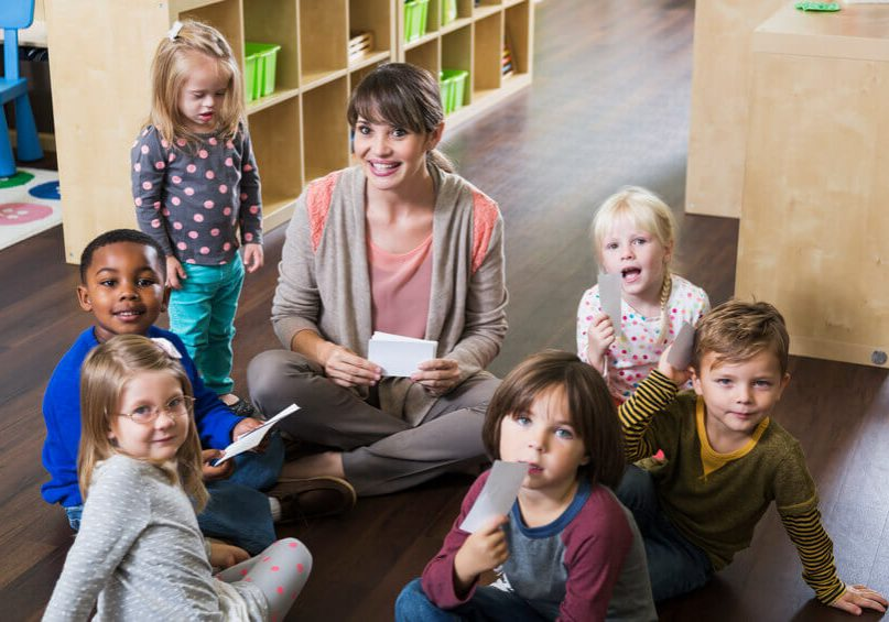A preschool teacher sitting on the floor with a group of multi-ethnic children in a circle, smiling at the camera.  A little girl, a special needs child with down syndrome, is standing beside her wearing a gray shirt with pink polka dots.