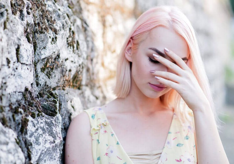 Worried teenager woman covering her face with hand, Scared woman